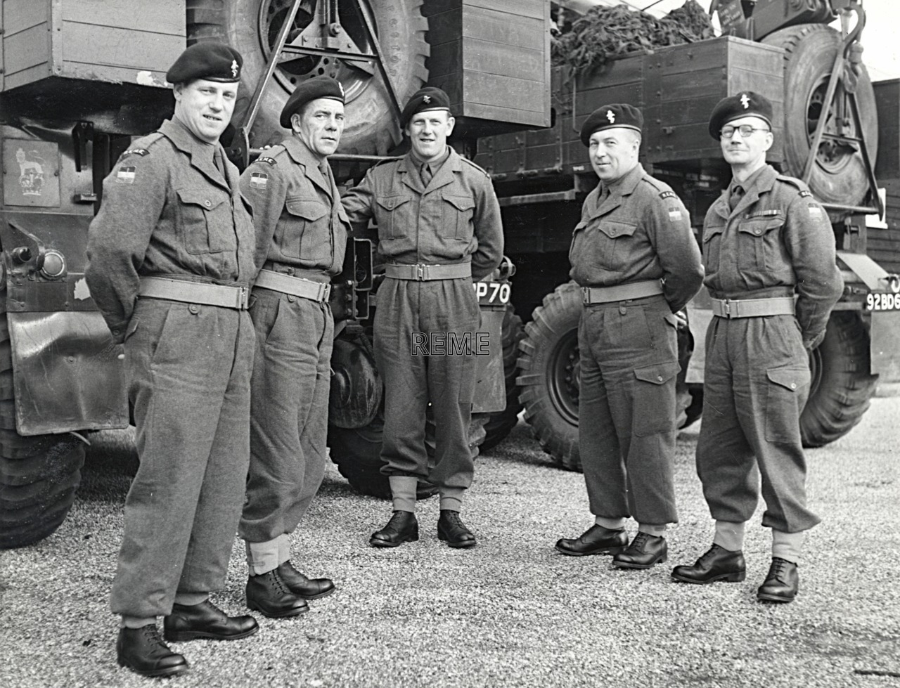 Five REME soldiers standing in front of two Scammells