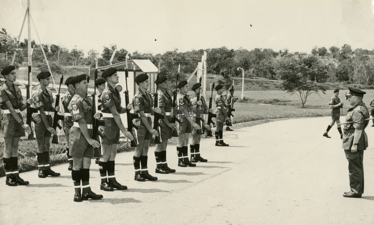 Major General L H Atkinson OBE, Director of Electrical and Mechanical Engineering (DEME) Ministry of Defence (Mindef) (War Office), takes the salute from a Guard of Honour
